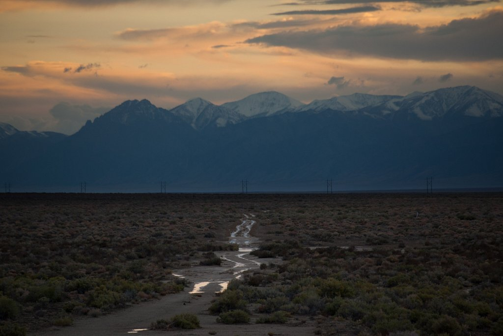 Water in road tracks against snow capped mountains at sunset