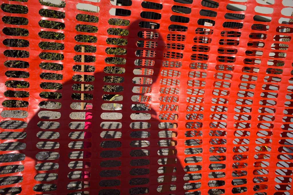 Orange plastic fence with shadow