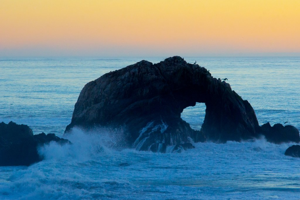 Birds and arch hole rock at dusk