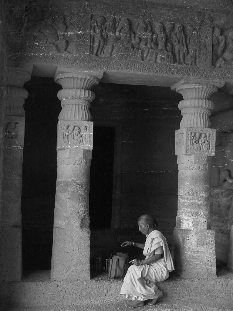Woman eating lunch between carved stone columns at Ajanta Caves