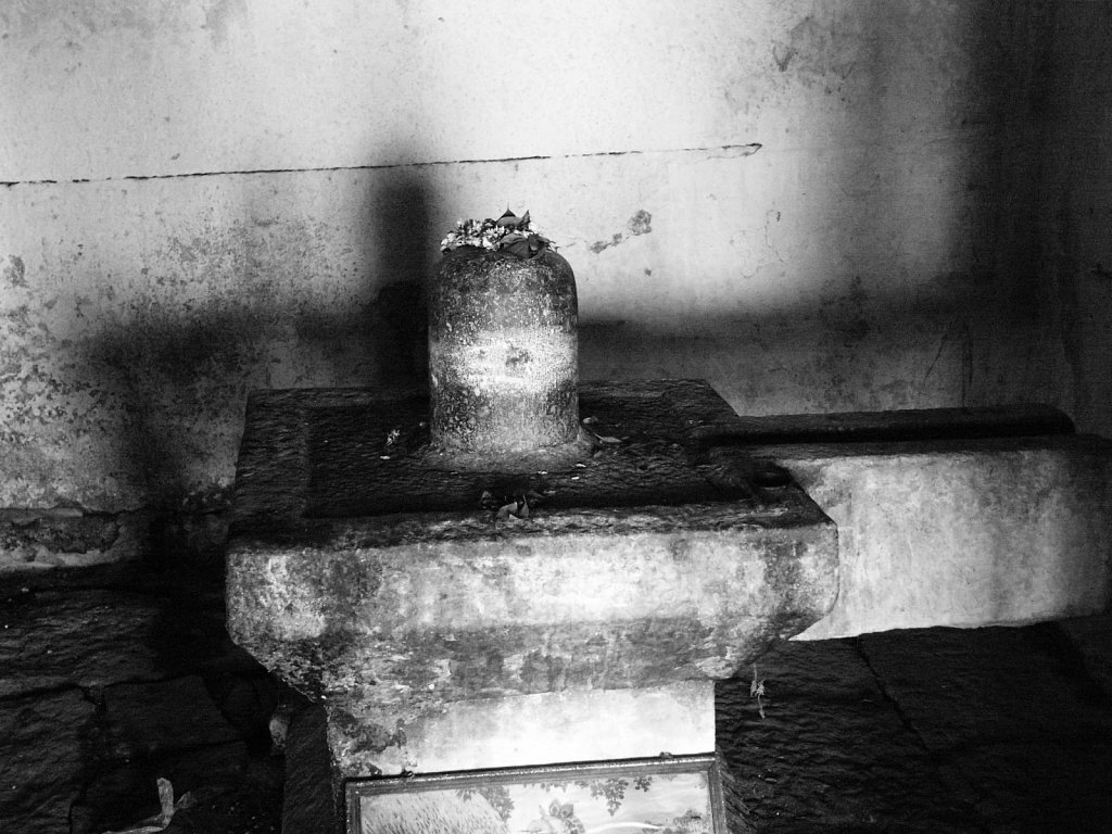 Lingam with flowers anointing it in a small shrine near Hampi