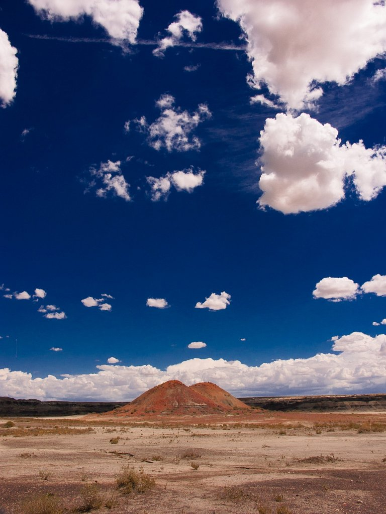 Deep blue sky fluffy clouds and painted hills in the Bisti Badla