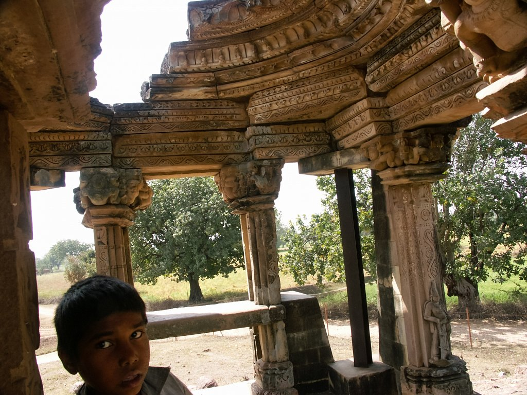 Boy sits in crumbling old temple shrine near Khajurao