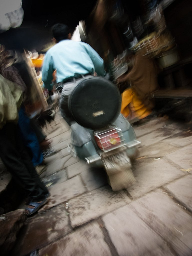 Scooter careens down back streets in Varanasi