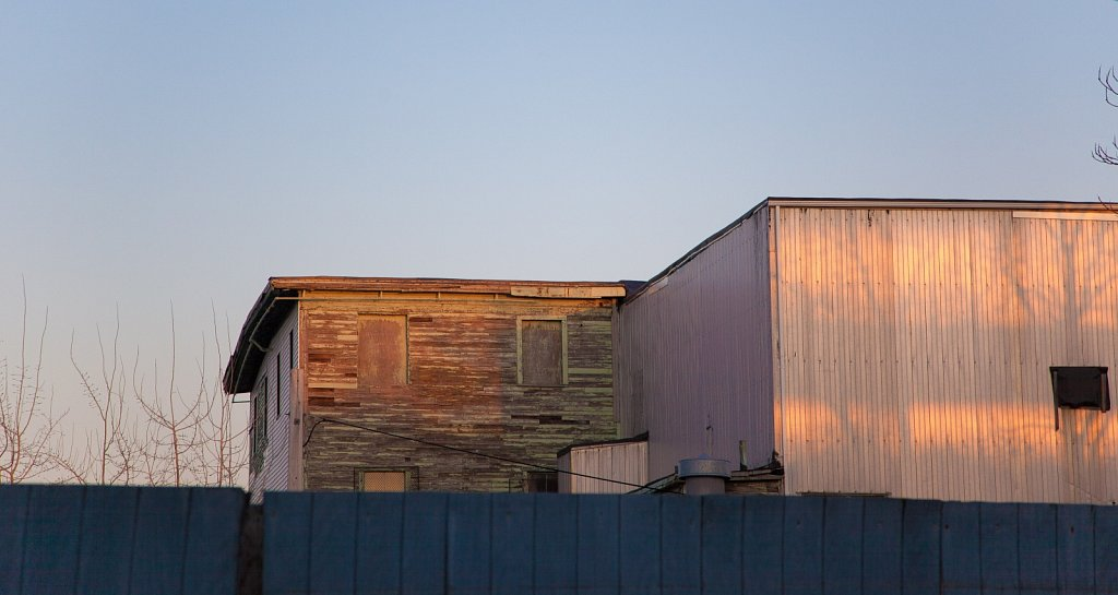 Blue fence and last light on an old wood and corrugated metal bu