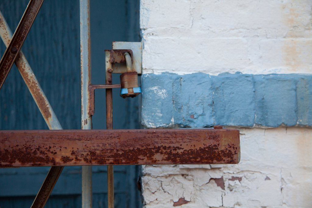 Closeup of a lock and a metal gate in front of a blue wooden doo