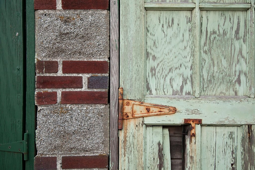 Old light green door and newer green door set in a stone and bri