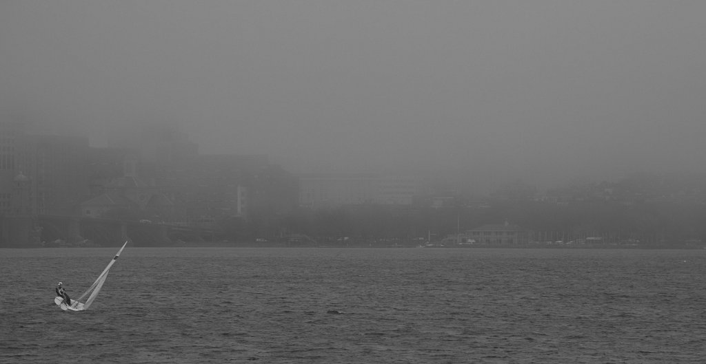 A lone sailboat on the Charles River, with a misty view of downt