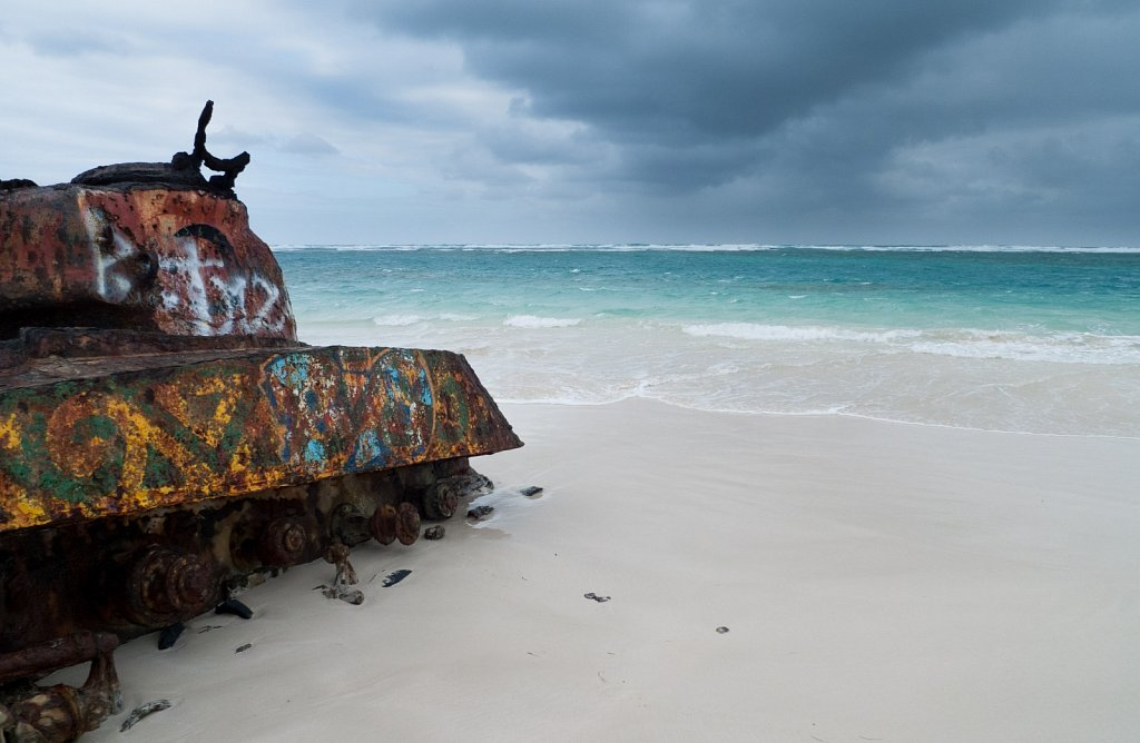 Military tank rests on a white sand beach in front of aquamarine