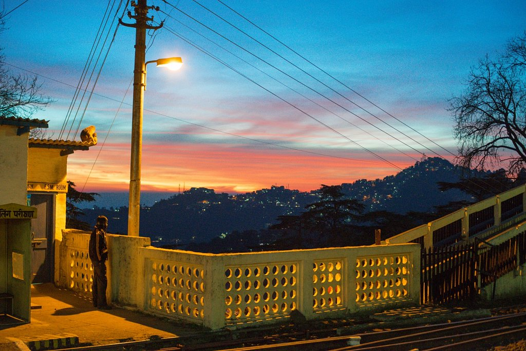 A man and a monkey look at the sunset over Summer Hill in Shimla